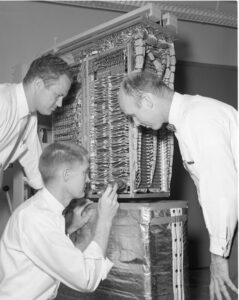 men examining a computer in the 1960s